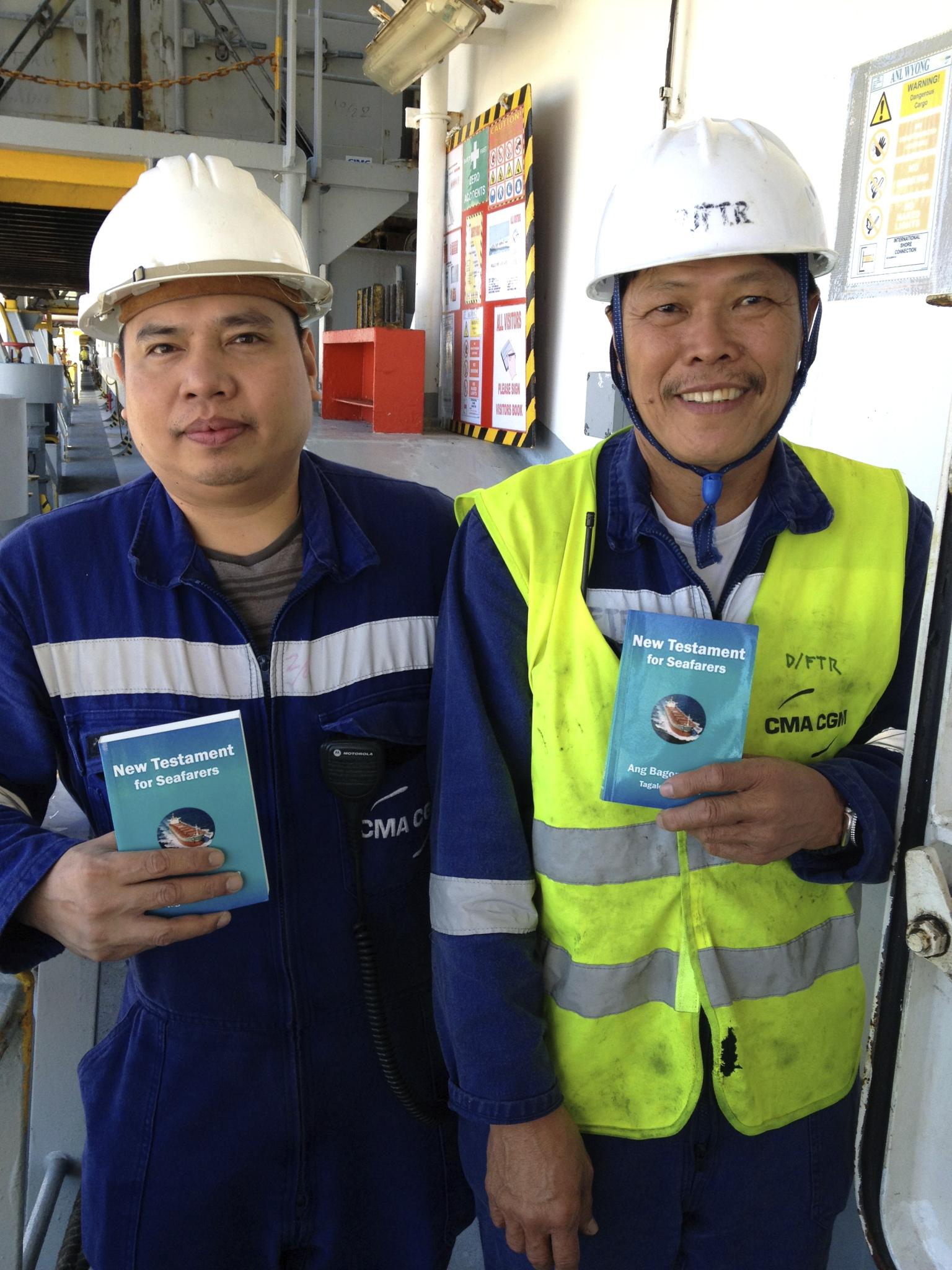 2 Philippino sailors with the bi-Lingual (English/Tagalog) NIV New Testaments