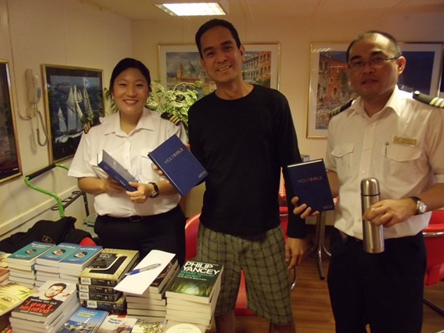 Woman getting her extra Bibles for the on board Fellowship group